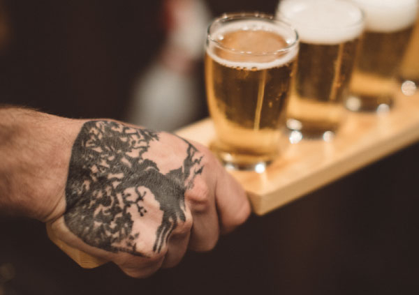 Bartender's hand holding a selection of Public House Brewing Company beers
